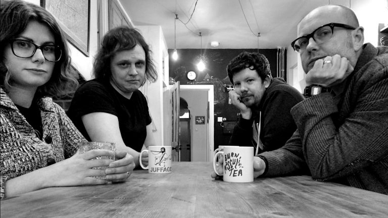 GodNo! black and white band image showing members at a kitchen table